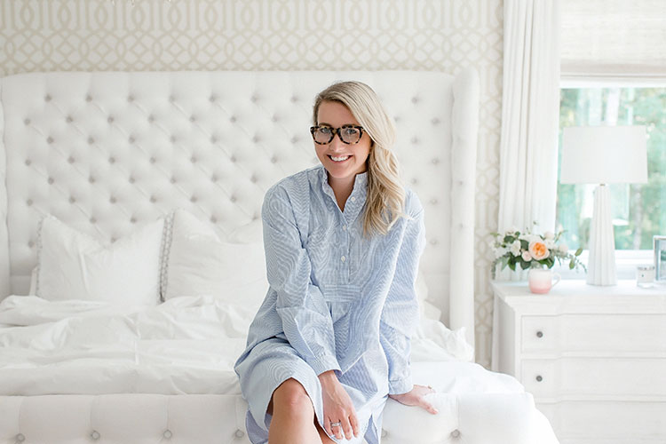 Monika Hibbs in blue gingham nightshirt sitting on bed